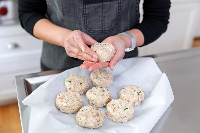 Forming gluten-free and keto crab cakes on a parchment paper lined plate.