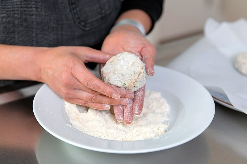 Someone coating a paleo crab cake with coconut flour.