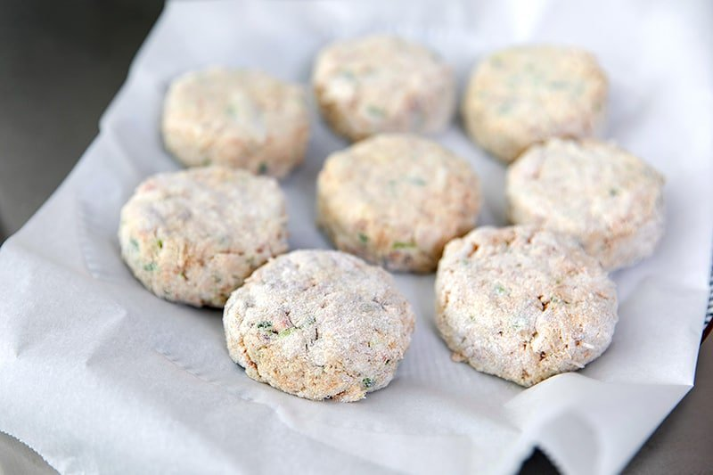 A parchment paper lined plate is filled with paleo crab cakes that are waiting to be fried.