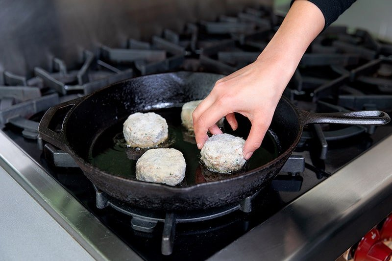 Adding paleo crab cakes to a cast iron frying pan.