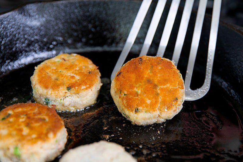 Flipping golden brown paleo crab cakes in a cast iron skillet with a metal fish spatula.