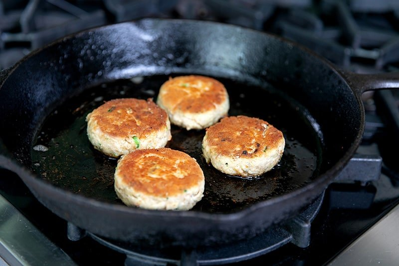 Four golden brown gluten-free crab cakes frying in a cast iron skillet.