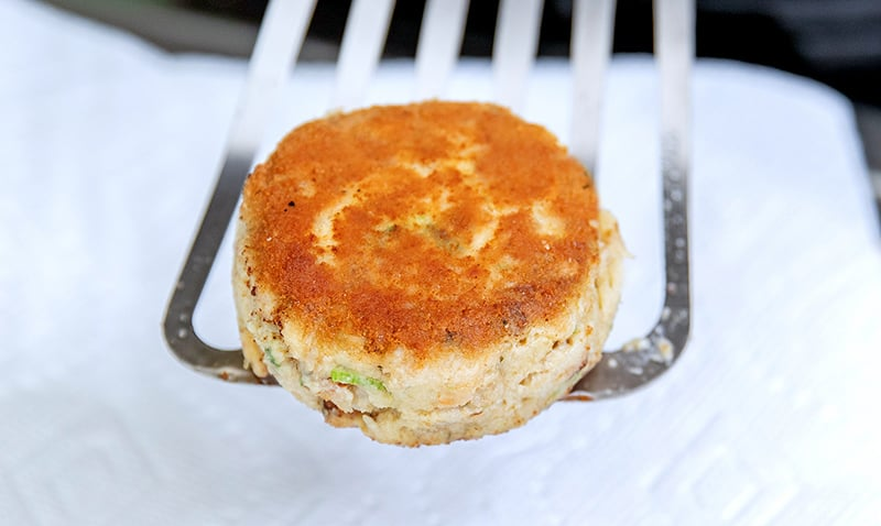 A closeup shot of a golden brown paleo and keto crab cake on a fish spatula.