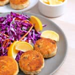 Two plates filled with paleo crab cakes, red cabbage slaw, and lemon wedges.