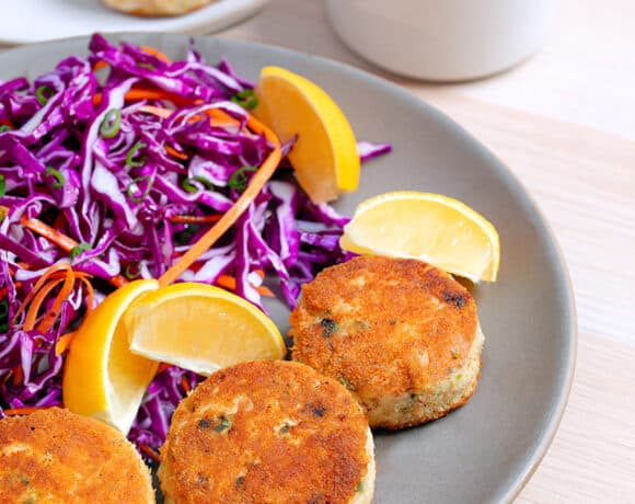 A plate filled with paleo crab cakes, red cabbage slaw, and lemon wedges.