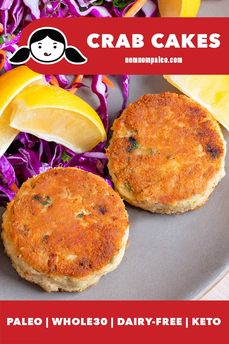 Two golden brown paleo crab cakes are on a beige plate, next to purple cabbage slaw and lemon wedges.
