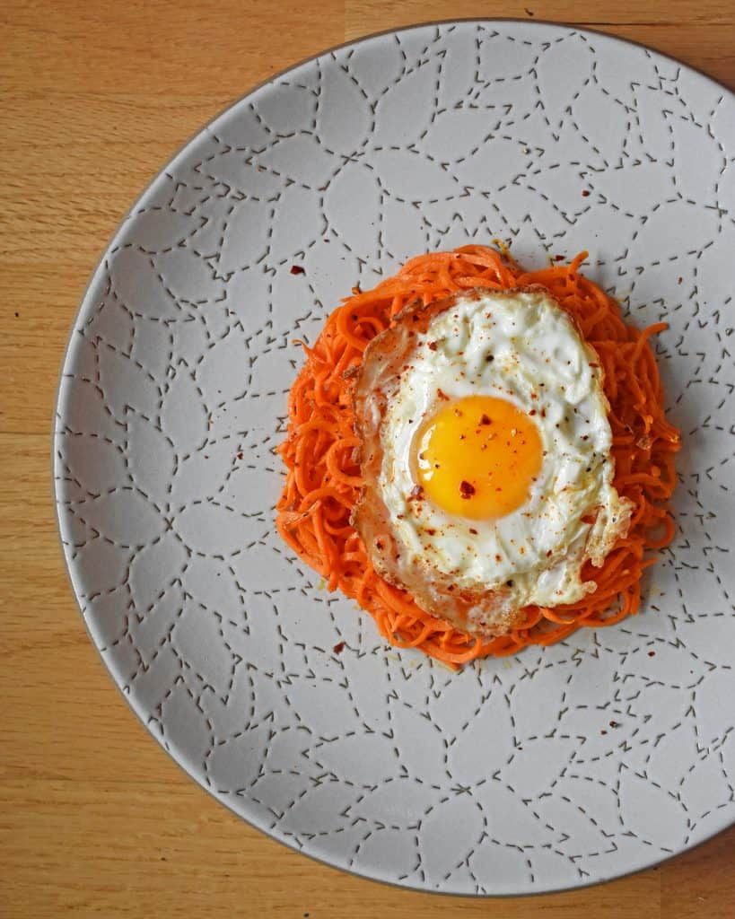 An overhead shot of Sweet Potato Hash with Fried Eggs on a white plate.