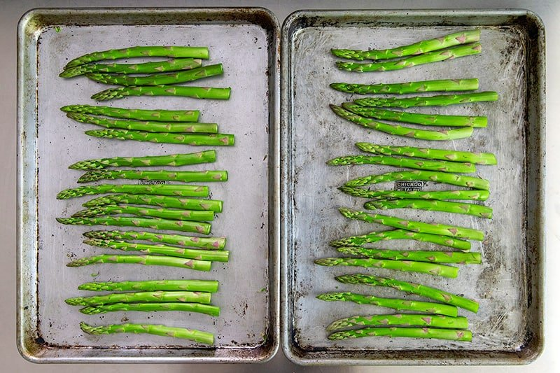 An overhead shot of the trimmed asparagus divided evenly onto two rimmed baking sheets.