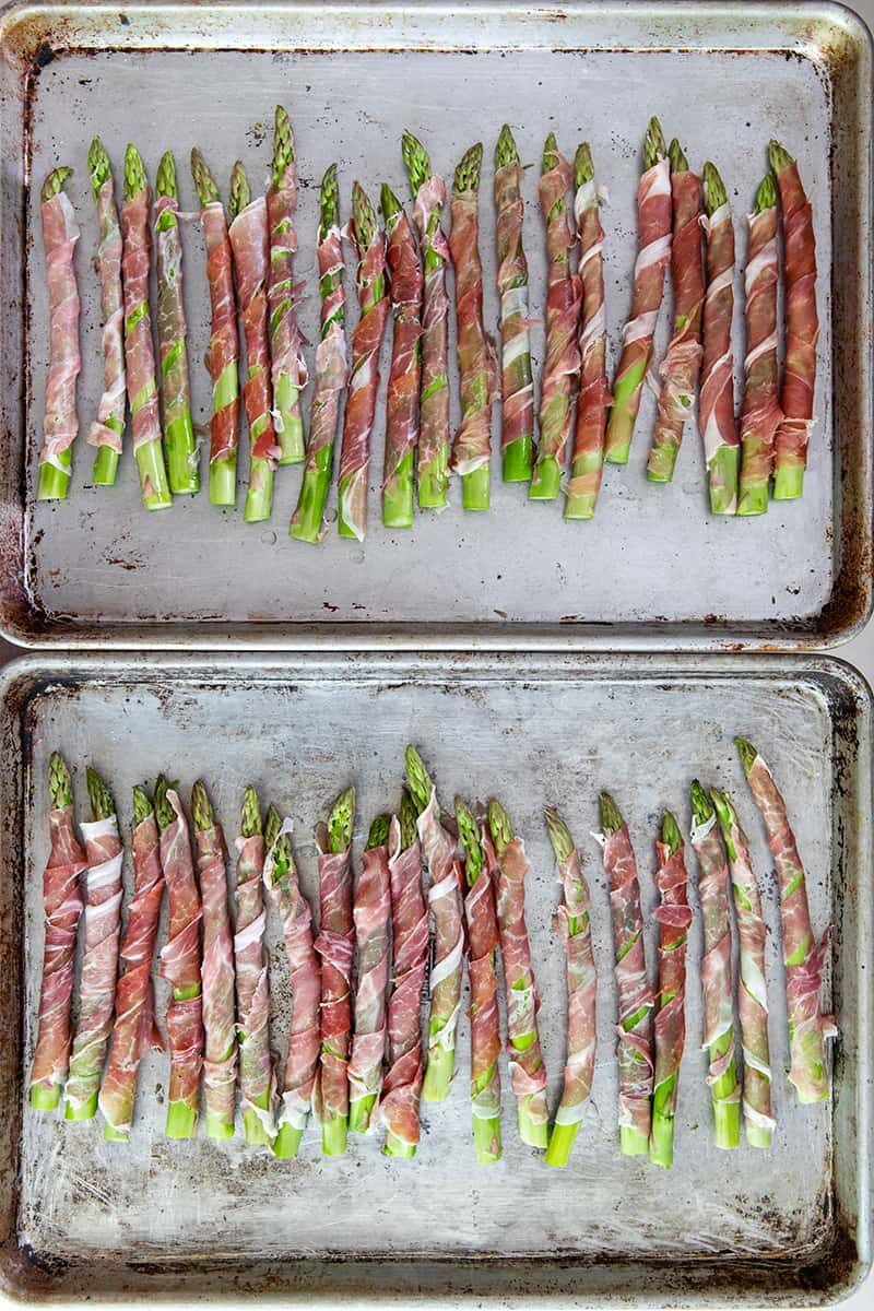 An overhead shot of two rimmed baking sheets filled with prosciutto-wrapped asparagus in a single layer.