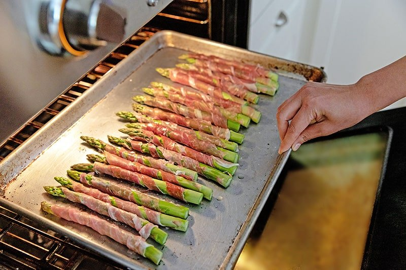 Someone placing a rimmed baking sheet of prosciutto-wrapped asparagus under the broiler in the oven.