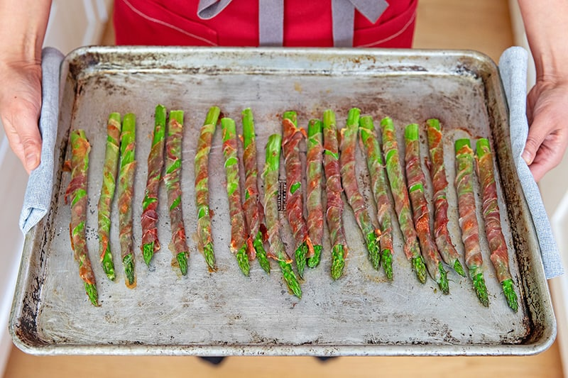 An overhead shot of a person holding a tray of prosciutto-wrapped asparagus.