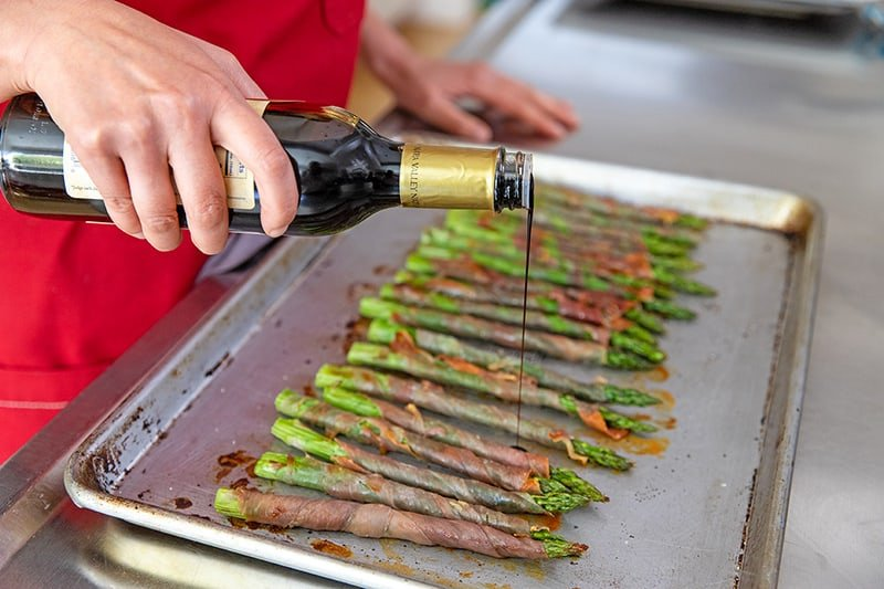 Someone adding aged balsamic to prosciutto-wrapped asparagus.