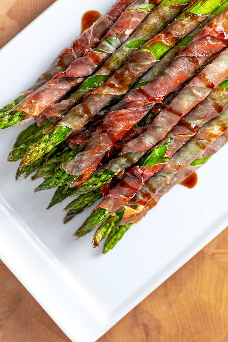 An overhead shot of prosciutto-wrapped asparagus on a white plate.