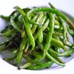 A closeup shot of roasted green beans in a white serving plate.