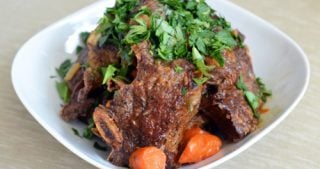 Beef short ribs topped with parsley in a bowl.