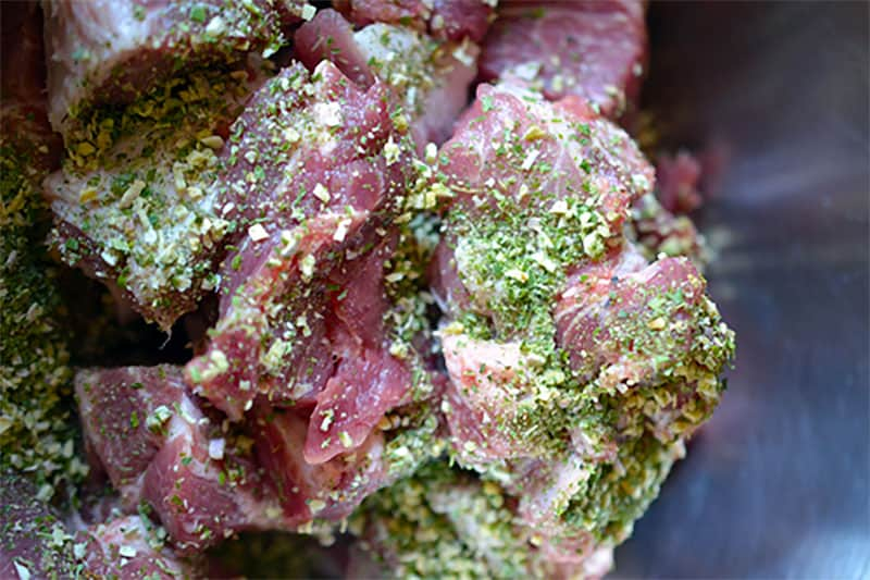 Raw pork shoulder cubes seasoned with Sunny Paris Seasoning.