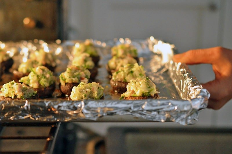 A tray of shrimp stuffed mushrooms being placed in the oven.
