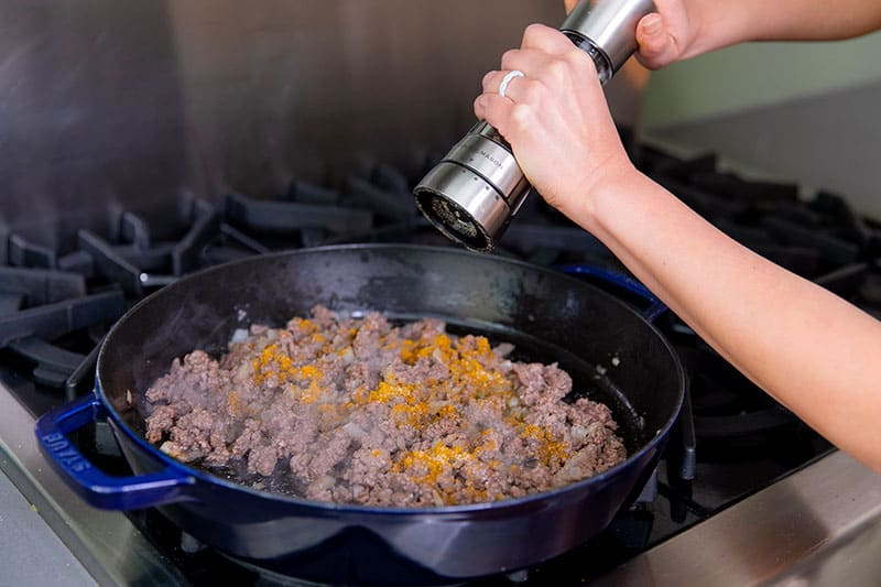 Someone cracking freshly ground black pepper in a pan filled with ground beef, diced onions, and Madras curry powder.