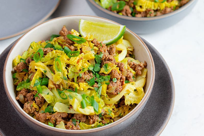 A closeup shot of a brown bowl filled with keto and paleo garbage stir-fry, a delicious ground beef and curried cabbage supper/