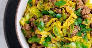 An overhead shot of an Indian-inspired beef and cabbage stir-fry with a lime wedge on the side.