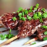 A closeup of Whole30-friendly steak skewers with cherry barbecue sauce.