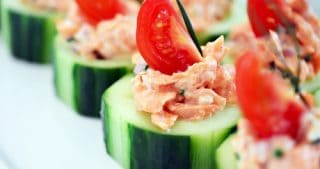 Spicy salmon on top of sliced cucumbers topped with cherry tomatoes.