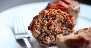 A plate with a paleo meatloaf muffin cut in half.