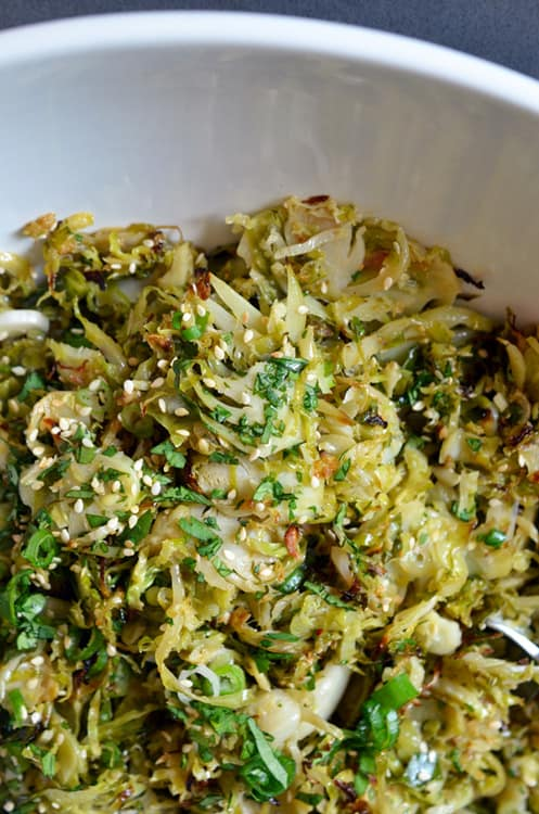 A closeup of a white bowl filled with Warm Brussels Sprouts Slaw with Asian Citrus Dressing