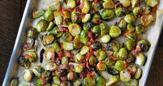An overhead shot of a rimmed baking sheet filled with Roasted Brussels sprouts with Bacon.