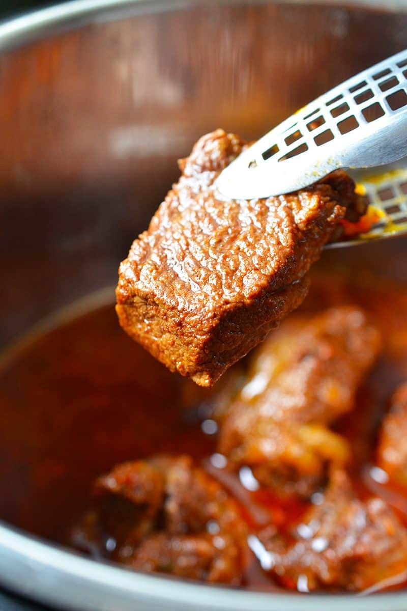 A pair of tongs is holding a piece of fork tender Instant Pot Mexican Beef