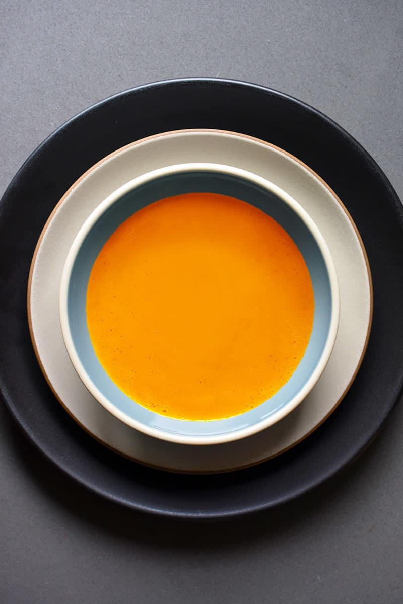 An overhead shot of Carrot Cardamom soup in a serving bowl.