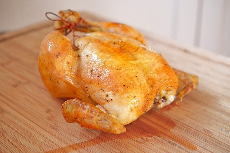 A closeup of Weeknight Roast Chicken on a wooden cutting board