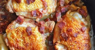 An overhead shot of a cast iron pan filled with pan-roasted chicken with bacon and apples
