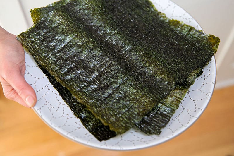 Someone holding a white plate with toasted nori sheets cut in half to make California hand rolls or Temaki.
