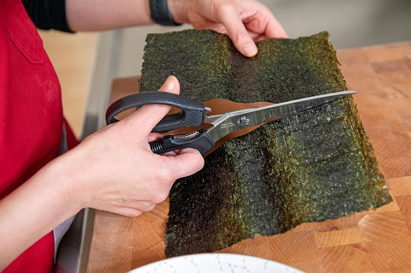 Someone using kitchen shears to cut a toasted sheet of nori in half width-wise to make Whole30 and keto California hand rolls.