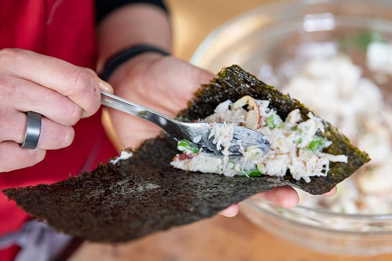 Someone adding the filling to the California hand roll on a rectangular piece of toasted nori.