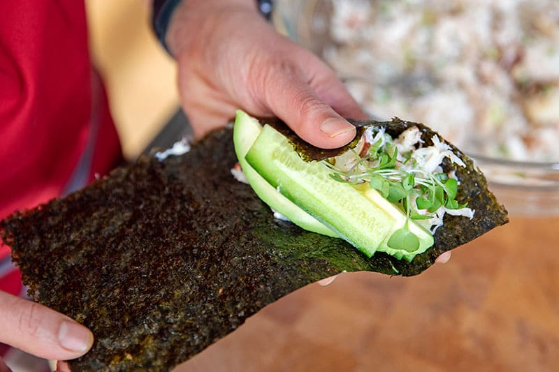 Adding the sliced cucumber, avocado, and sprouts on top of the crab salad on a piece of nori.