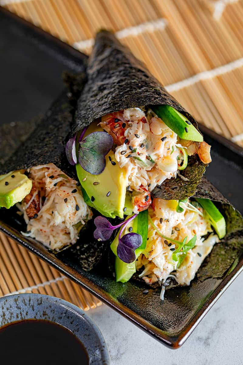 Three gluten-free and Whole30 California hand rolls stacked on a black plate, next to a dipping bowl with coconut aminos.