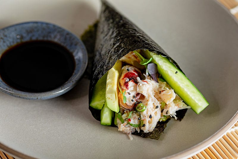 Closeup up of a homemade California hand roll filled with crab, avocado, and cucumbers.