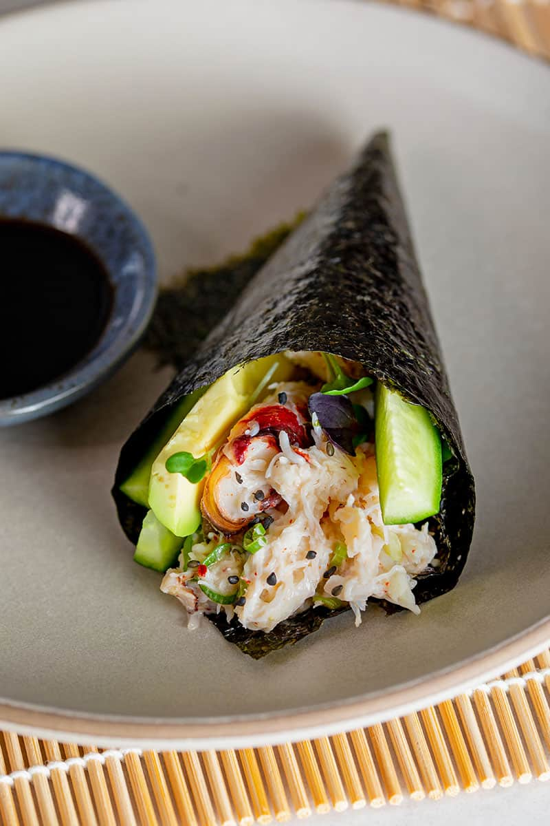 A closeup of a California hand roll on a gray plate next to a small bowl filled with coconut aminos.