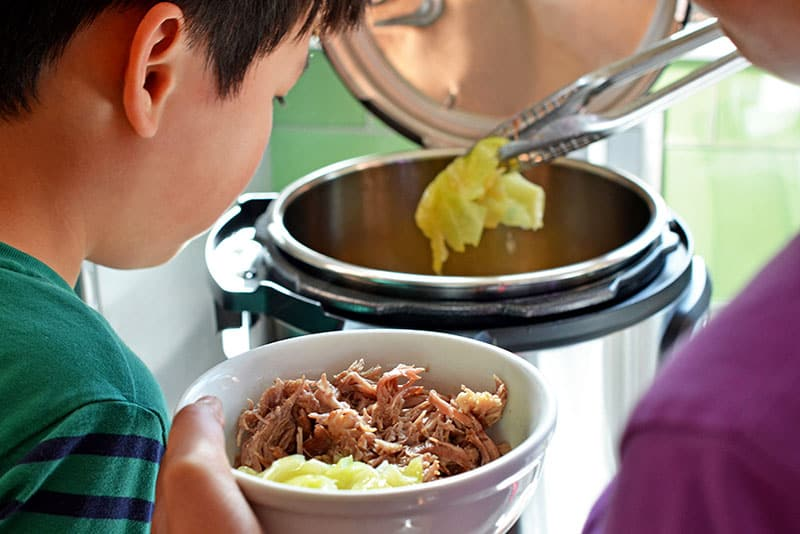 A young boy watching a woman use tongs to serve Instant Pot Kalua Pig in a white bowl.
