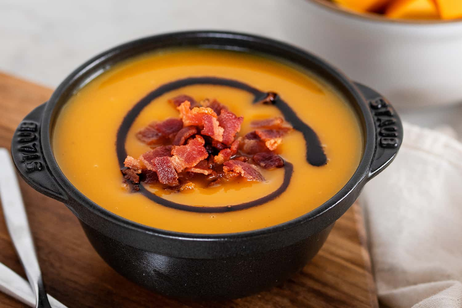A closeup of a black bowl filled with Instant Pot Butternut Squash Soup, topped with crispy bacon bits and aged balsamic vinegar.