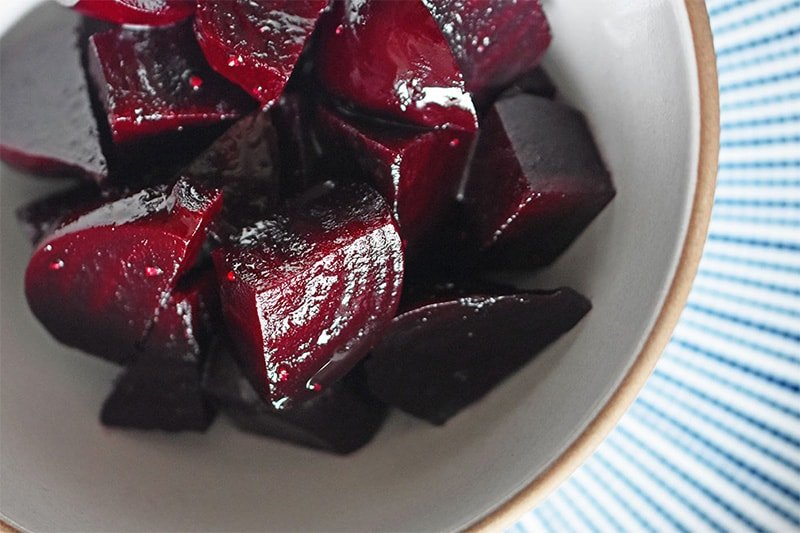 An overhead shot of Instant Pot Beets in a white bowl on top of a blue and white plate.