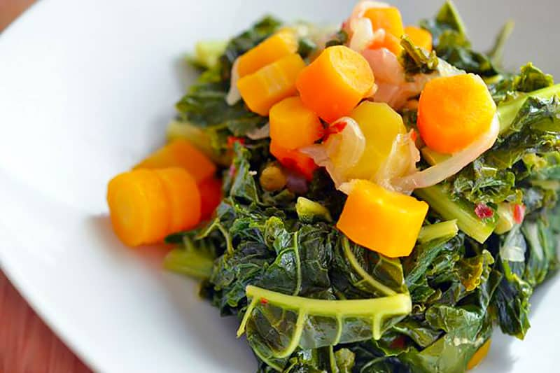 A closeup shot of a white plate filled with Pressure Cooker Braised Kale and Carrots