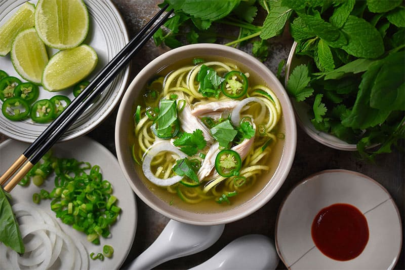 An overhead shot of a bowl of Instant Pot Chicken Pho surrounded by herbs and condiments.