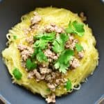 An overhead shot of a bowl of Instant Pot spaghetti squash topped with stir-fried ground pork and cilantro leaves.