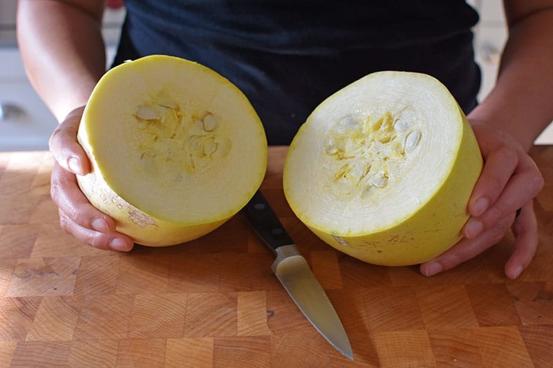 A spaghetti squash is cut in half horizontally with a small paring knife.