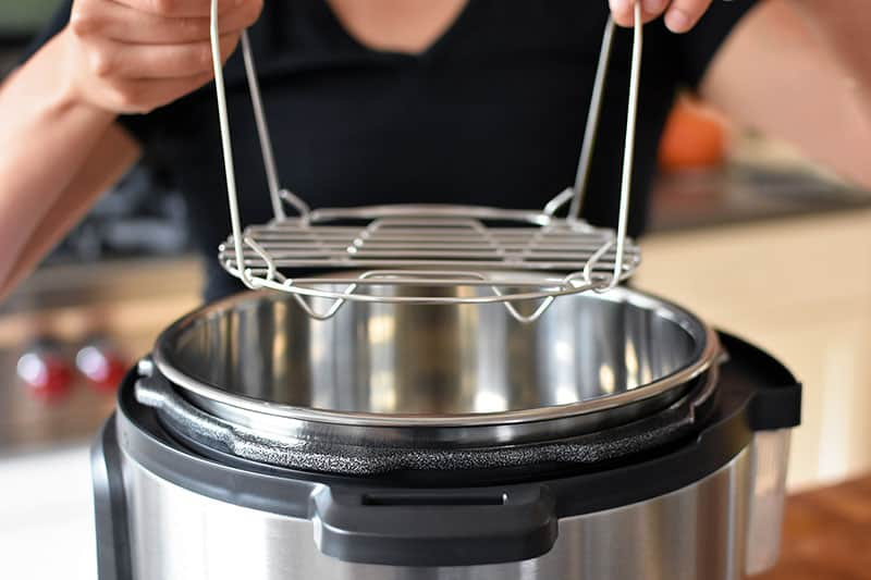 A closeup of two hands lowering a stainless steel steaming rack into an open Instant Pot.