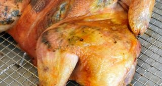 A side view of a spatchcocked chicken with herb butter fresh out of the oven
