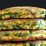 A stack of paleo egg foo young against a black background